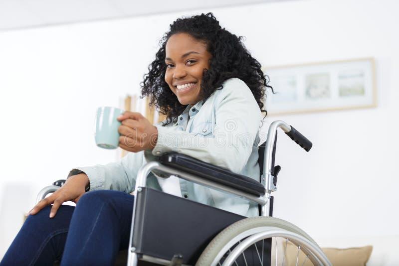 食用的轮椅的年轻办公室工作者茶或咖啡 免版税图库摄影