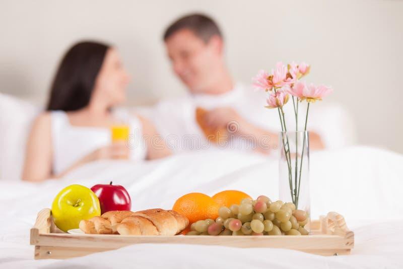 食用美好的微笑的年轻的夫妇早餐 免版税库存图片