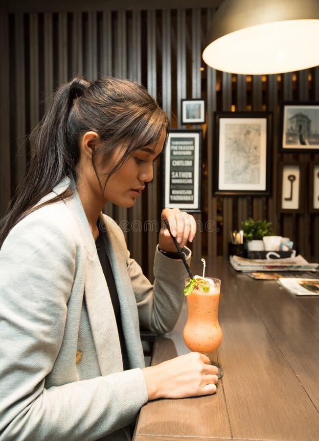 食用职业妇女边的背面图饮料果汁 免版税图库摄影