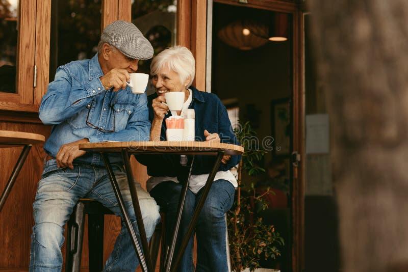 食用资深的夫妇放松在咖啡馆和咖啡 免版税图库摄影