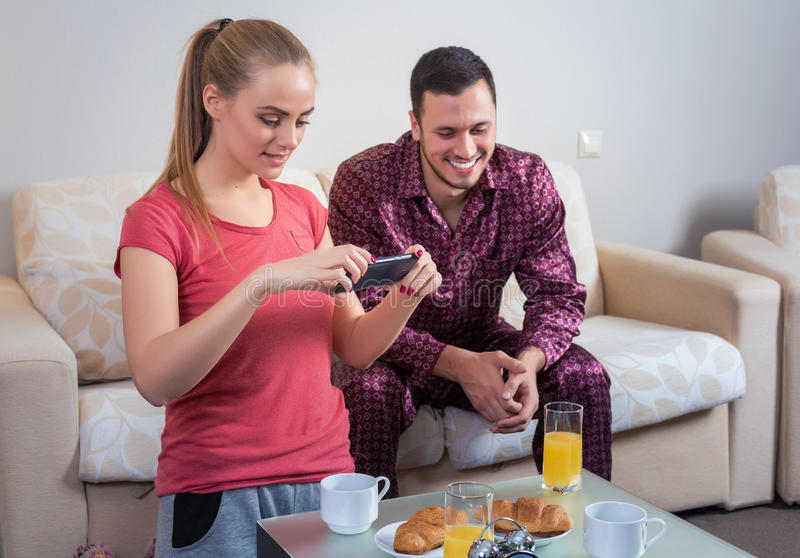 食用逗人喜爱的年轻的夫妇早餐,在手机的照片 图库摄影