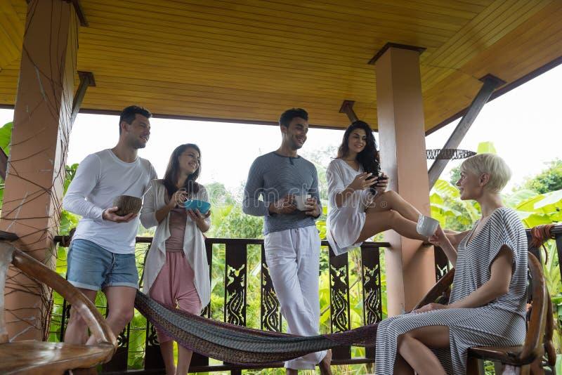 食用青年人的小组在大阳台热带旅馆,朋友热带假日假期的早餐 免版税库存照片
