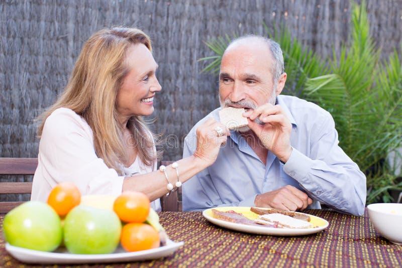 食用年长的夫妇在大阳台的食物 库存照片