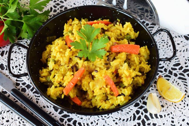 素食米用红萝卜,葱、raisans和橄榄油在一种黑金属滚保龄球 概念吃健康 节食 库存照片