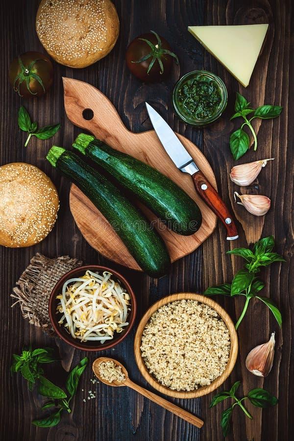 素食者炸肉排或小馅饼为汉堡做准备 夏南瓜奎奴亚藜素食者汉堡用pesto调味汁和新芽 顶视图,顶上 免版税图库摄影