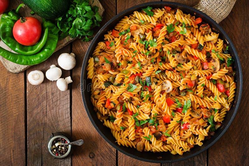 素食菜面团Fusilli用夏南瓜、蘑菇和雀跃在平底锅在木桌上 免版税库存图片
