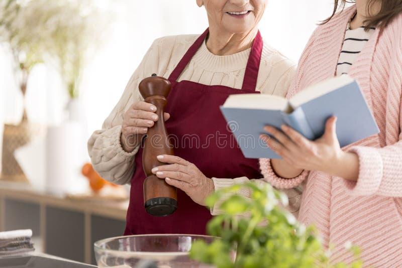 读食谱书的祖母和孙女 免版税库存照片