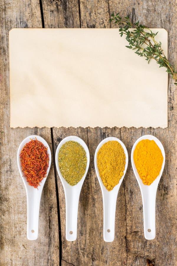 食谱香料背景 与老纸板料的各种各样的辣混合用麝香草 免版税库存图片
