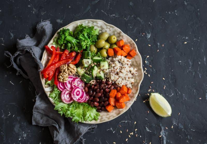 素食食物碗 奎奴亚藜,豆,白薯,硬花甘蓝,胡椒,橄榄,黄瓜,坚果-健康午餐 在黑暗的桌上 免版税库存图片