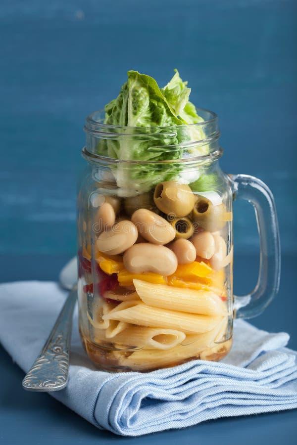 素食主义者在金属螺盖玻璃瓶的意大利面制色拉用菜豆橄榄 库存照片