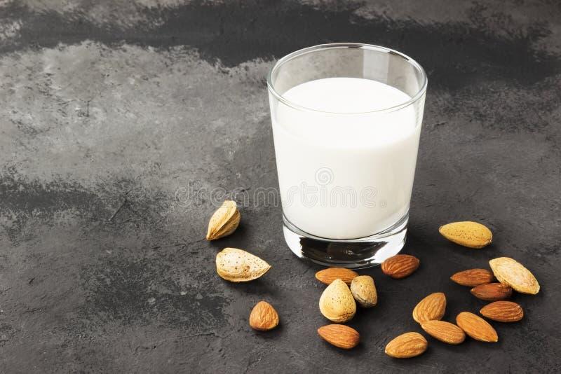 素食主义者在玻璃的杏仁牛奶在黑暗的背景 不含乳制品的牛奶 免版税库存照片