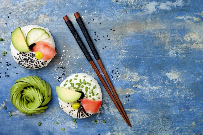 素食主义者寿司油炸圈饼设置了用烂醉如泥的姜、鲕梨、黄瓜、香葱、nori和芝麻在蓝色背景 寿司食物杂种趋向 库存图片