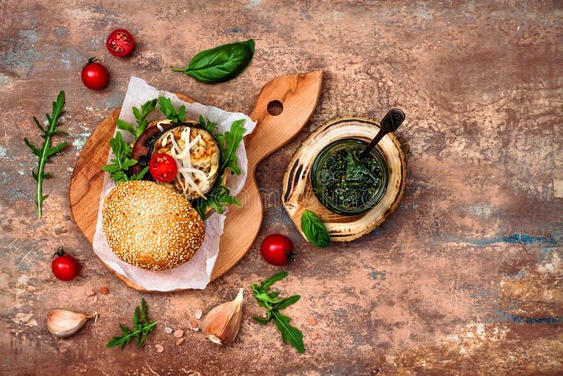 素食主义者烤了茄子、芝麻菜、新芽和pesto汉堡 素食者甜菜和奎奴亚藜汉堡 顶视图,顶上,平的位置 复制空间 库存图片