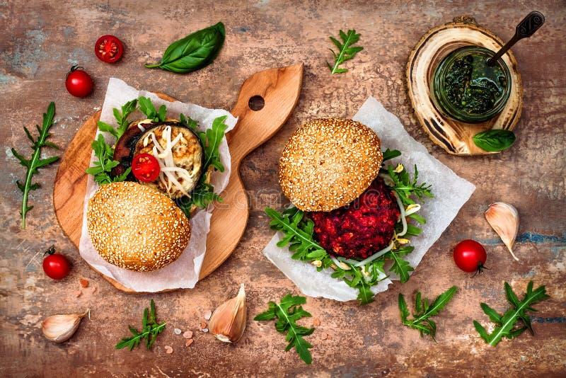 素食主义者烤了茄子、芝麻菜、新芽和pesto调味汁汉堡 素食者甜菜和奎奴亚藜汉堡 顶视图,顶上,平的位置 库存图片