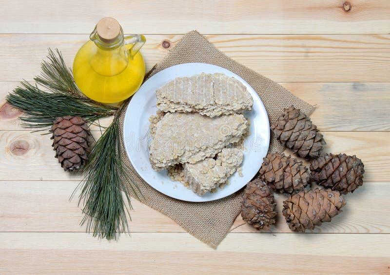 素食主义者的食物 在一个玻璃瓶的雪松油有雪松在板材的油饼的 免版税图库摄影