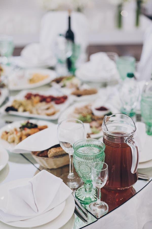 餐厅前台的婚礼豪华桌 时尚的酒杯、餐巾盘、餐具和桌上食物 免版税库存图片