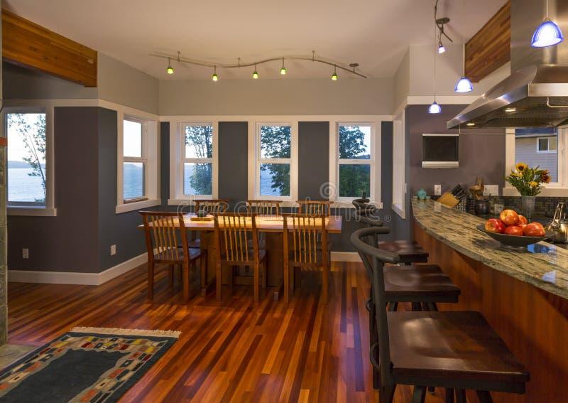 餐厅和厨房与木地板和花岗岩工作台面的早餐吧台在当代高级家庭内部 库存图片