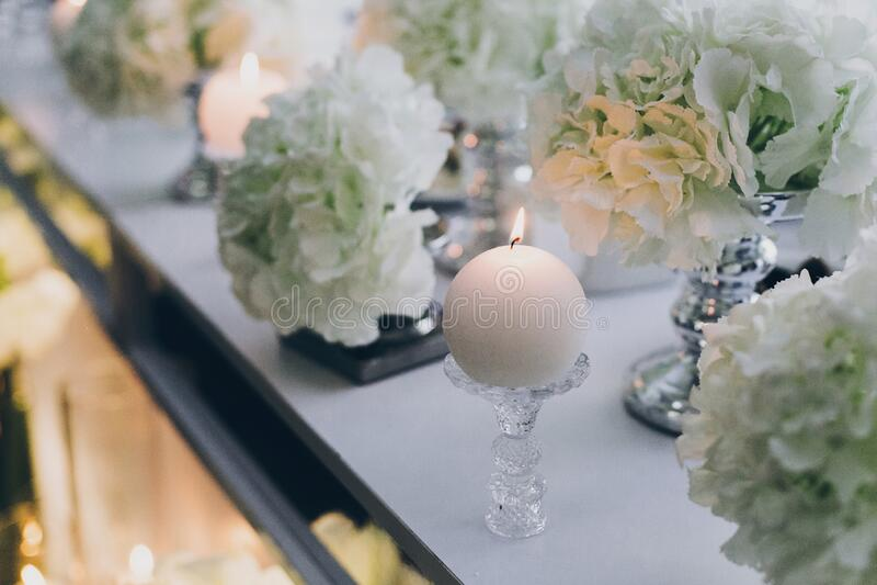 餐厅晚婚会的现代装饰 时尚的白色绣球花和现代的白色蜡烛,桌上有光 免版税库存图片