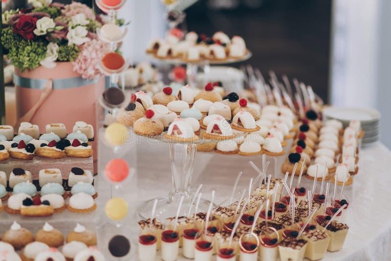 餐厅的婚宴上,在桌上提供美味的奶油甜点,包括水果、芭娜柯塔、蛋糕和饼干 奢侈 免版税库存图片