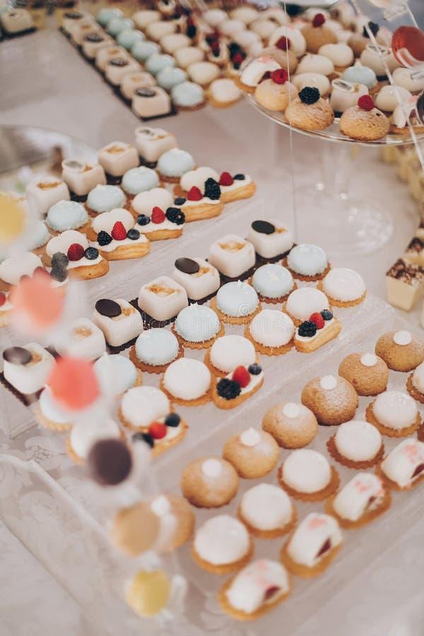 餐厅的婚宴上,在桌上提供美味的奶油甜点,包括水果、麦卡龙、蛋糕和饼干 豪华餐饮 免版税库存照片