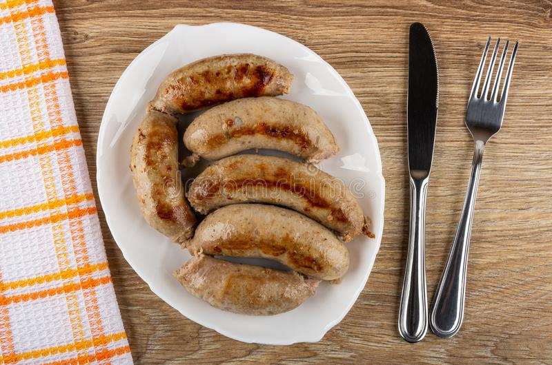 餐巾,在白色盘,刀子,在木桌上的叉子的炸鸡香肠 r 免版税库存照片