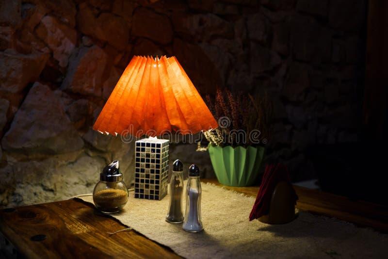 餐馆与盐的桌光和胡椒和餐巾 库存图片