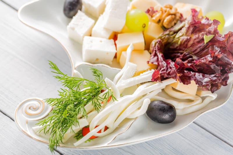 餐馆乳酪盘子-乳酪的各种各样的类型用葡萄和黑橄榄在白色板材 关闭与选择聚焦的图象 库存图片
