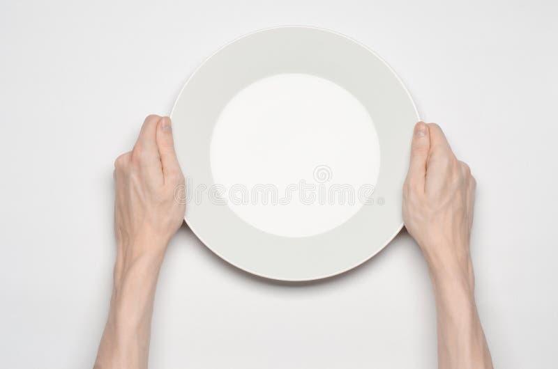 餐馆和食物题材:在一块空的白色板材的人的手展示姿态在白色背景在演播室隔绝了顶视图 免版税库存图片