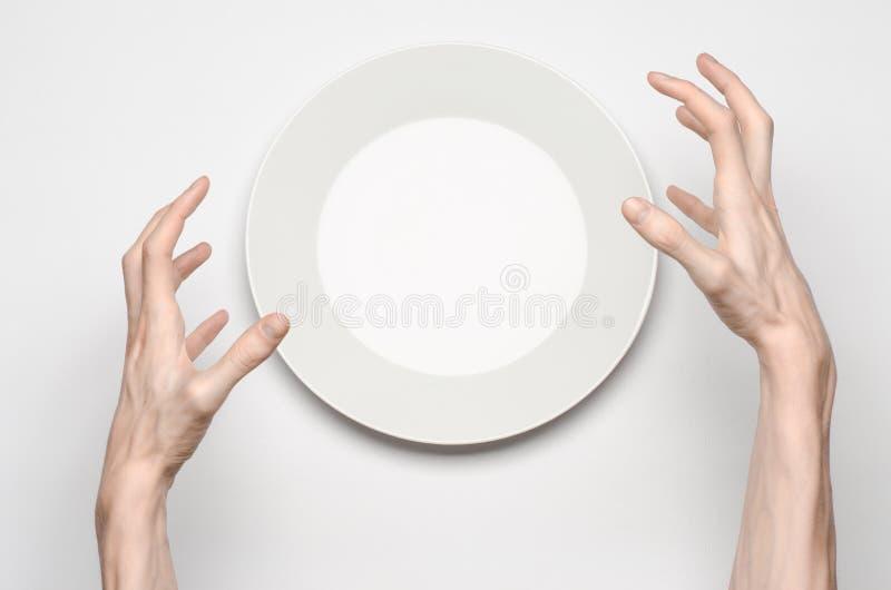 餐馆和食物题材:在一块空的白色板材的人的手展示姿态在白色背景在演播室隔绝了顶视图 图库摄影