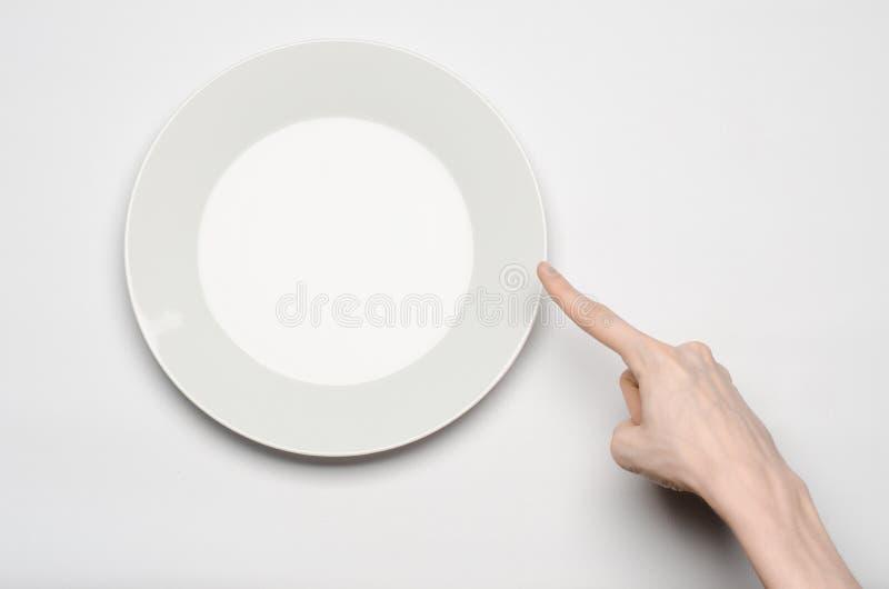 餐馆和食物题材:在一块空的白色板材的人的手展示姿态在白色背景在演播室隔绝了顶视图 库存照片