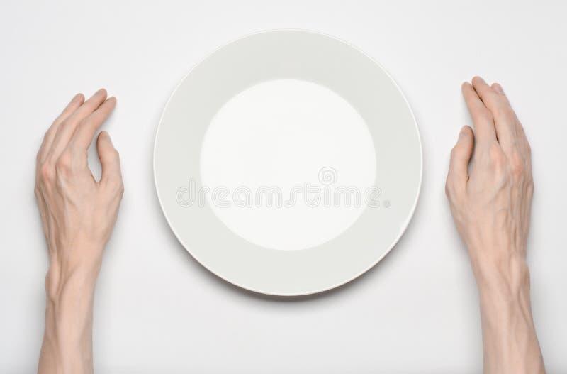 餐馆和食物题材:在一块空的白色板材的人的手展示姿态在白色背景在演播室隔绝了顶视图 免版税库存照片