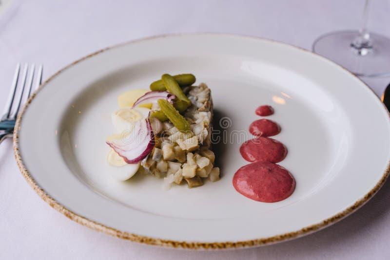 餐馆在一张紫色桌布的纤巧盘 白色板材用鲱鱼 免版税图库摄影