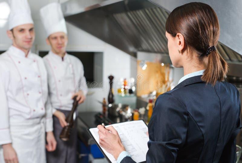 餐馆对他的厨房职员的经理简报在商业厨房里 库存图片