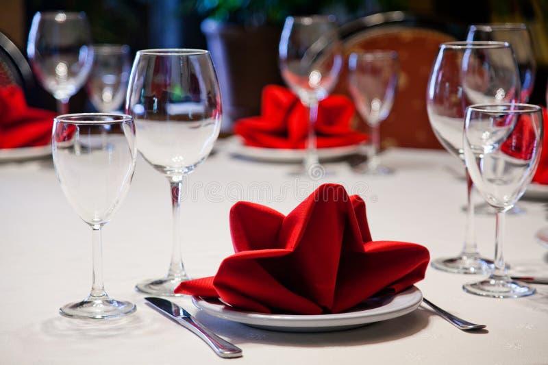 餐馆服务为佐餐葡萄酒玻璃和板材服务 白色桌布、红色餐巾、陶器和利器 免版税库存图片