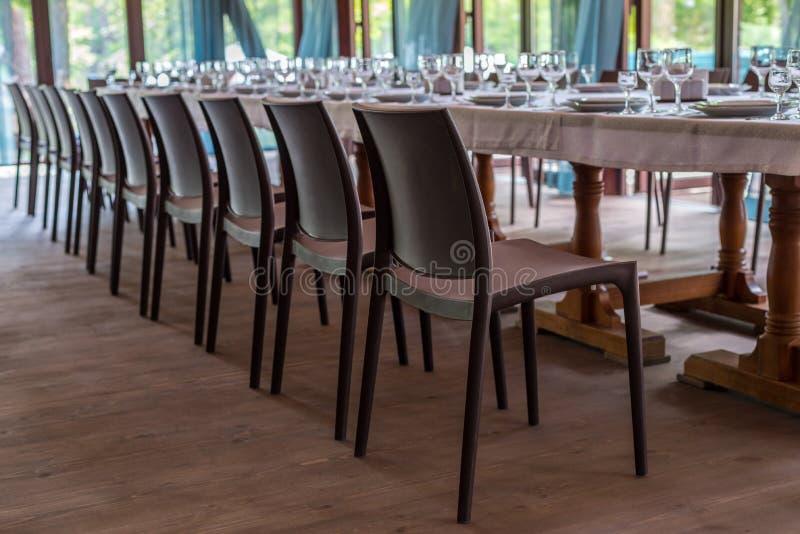 餐馆的内部,咖啡馆 与器物,板材、wiches、刀子、玻璃和酒杯和褐色椅子的表, prepar 库存图片