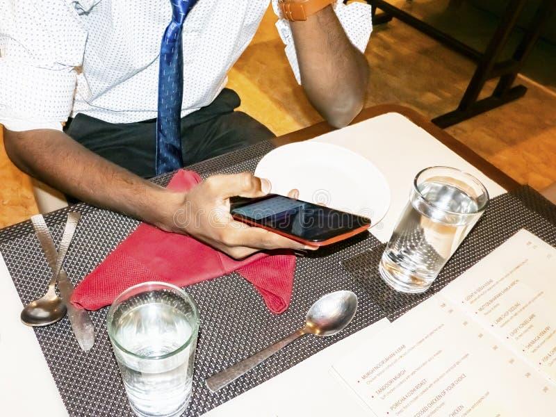 餐馆的年轻人印度成人学生有智能手机的 免版税图库摄影