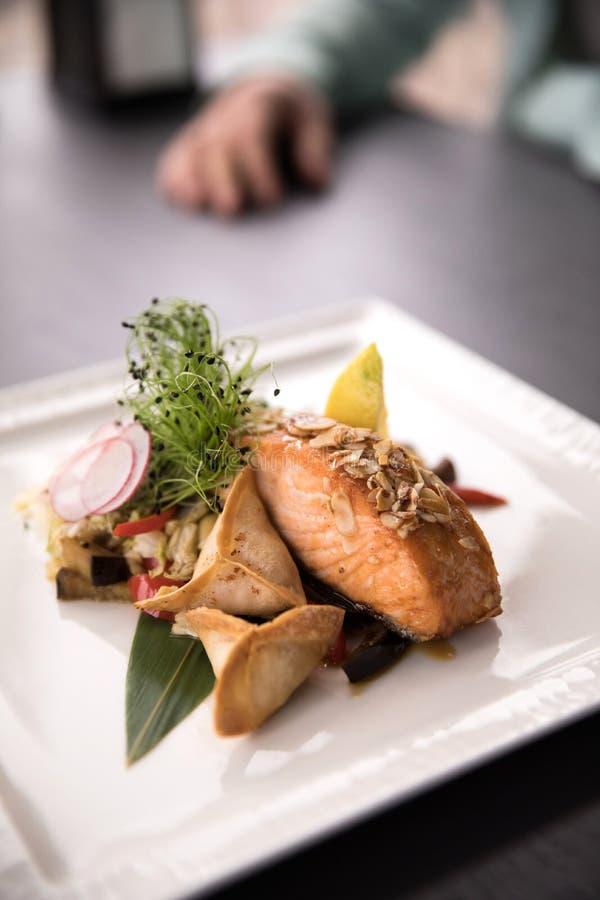 餐馆盘 在板材的美丽和鲜美食物 油煎的三文鱼用在板材的新鲜的沙拉 图库摄影