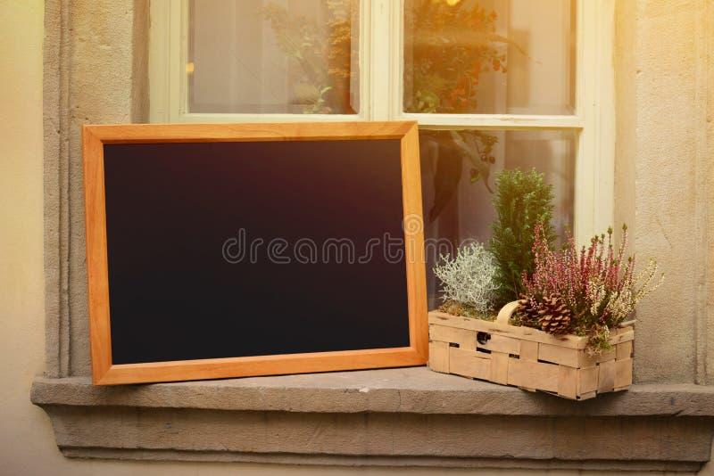 餐馆菜单的木板以增加文本的空的空间站立在widnow 免版税库存照片