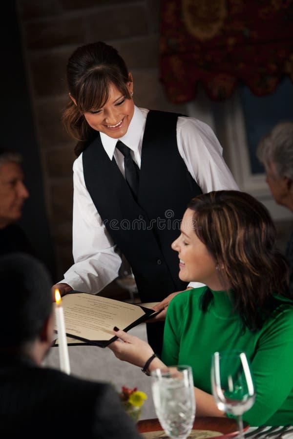 餐馆:服务器递菜单给顾客 免版税库存图片