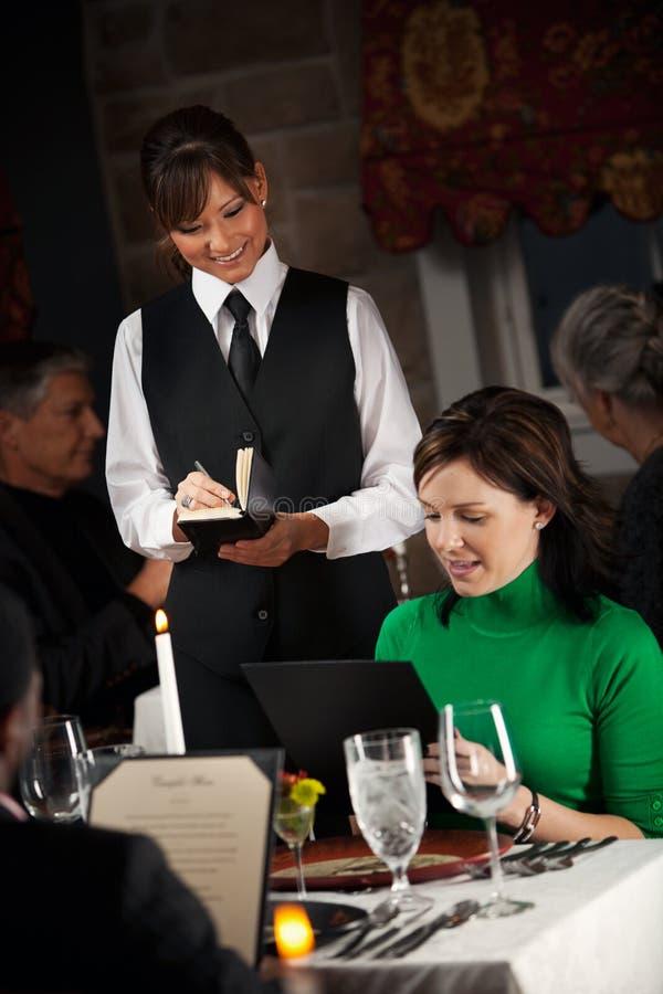 餐馆:从菜单的妇女预定的晚餐 免版税库存照片