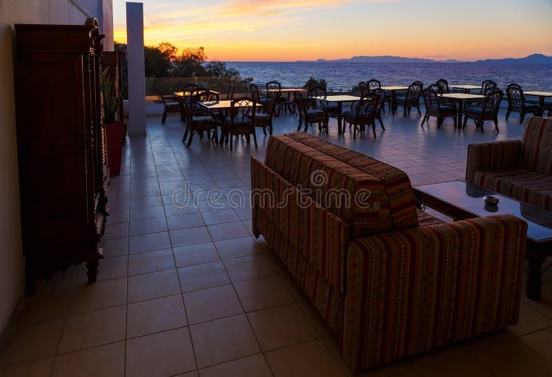 餐馆玻璃桌大阳台有海视图和美好的日落 库存图片