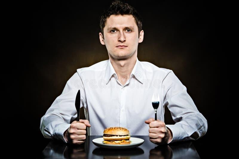 饥饿的人吃汉堡 图库摄影