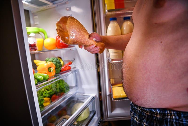 饥饿的人在他的手和身分下t上的握火鸡腿 库存照片