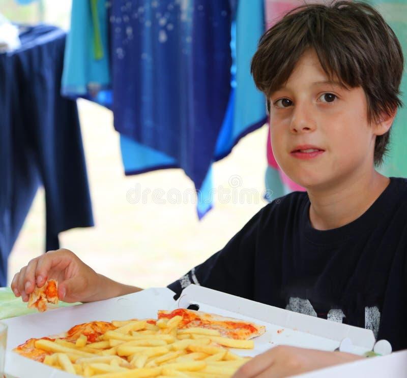 饥饿的孩子吃薄饼用无盐干酪乳酪并且油煎 库存照片