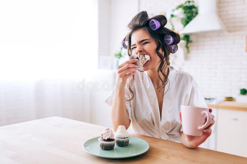 饥饿的年轻女人坐在桌上并且吃与奶油的薄煎饼在上面 举行杯子在手上 早晨白天 r 免版税库存照片