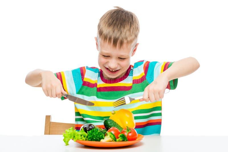 饥饿的男孩与菜板材,概念照片饮食的10岁 免版税库存图片