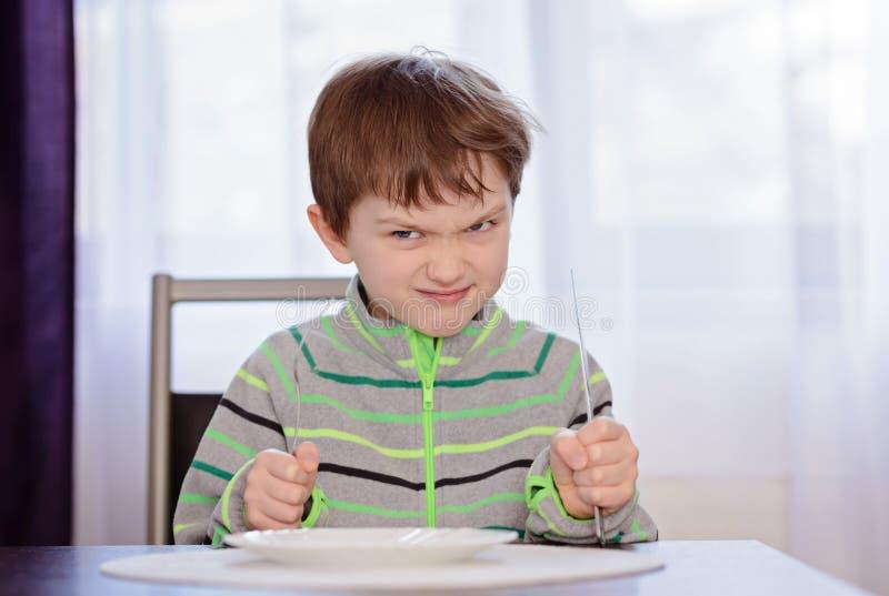 饥饿的男孩儿童等待的晚餐 免版税图库摄影
