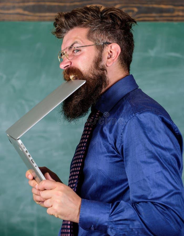 饥饿的知识人 他需要新的信息 知识干渴  老师有胡子的人咬住现代膝上型计算机 免版税库存图片