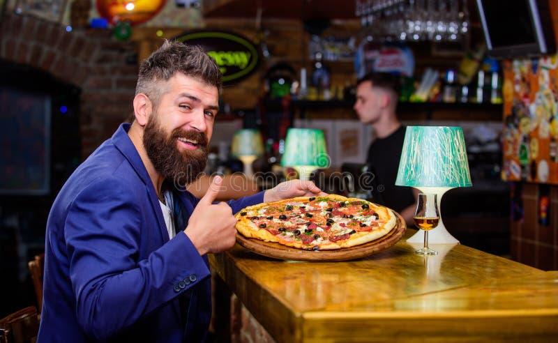 饥饿的行家吃意大利比萨 行家客户坐在酒吧柜台 人接受了可口比萨 享受您的膳食 免版税库存图片