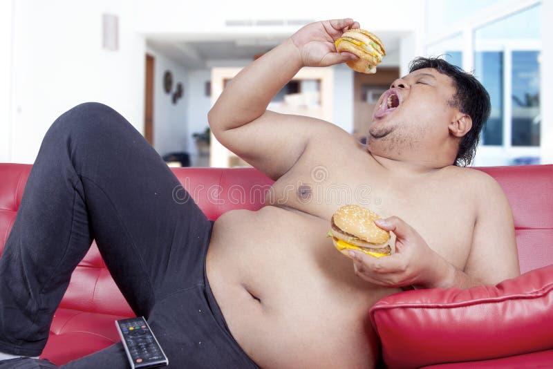 饥饿的超重人在家吃汉堡 免版税库存照片